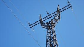 Torre ad alta tensione contro i cavi del cielo blu di una tecnologia di elettricità Fotografia Stock