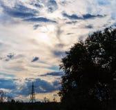 Torre ad alta tensione delle nuvole degli alberi drammatici delle siluette Fotografie Stock Libere da Diritti