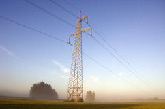 Torre ad alta tensione di postHigh-tensione sul campo dell'azienda agricola in foschia Immagini Stock Libere da Diritti