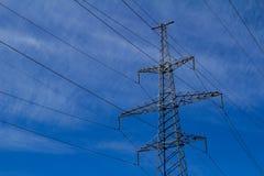 Torre ad alta tensione elettrica con la linea elettrica contro il cielo blu delle nuvole Immagine Stock Libera da Diritti