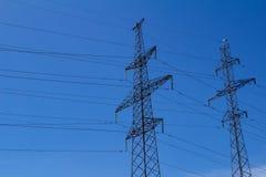 Torre ad alta tensione elettrica con la linea elettrica contro il cielo blu delle nuvole Fotografia Stock Libera da Diritti