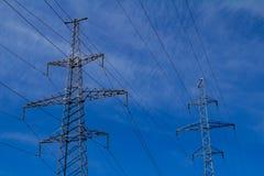 Torre ad alta tensione elettrica con la linea elettrica contro il cielo blu delle nuvole Immagini Stock Libere da Diritti
