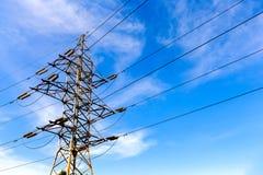 Torre ad alta tensione elettrica su un fondo del cielo blu Fotografia Stock