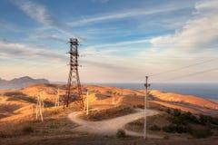Torre ad alta tensione in montagne al tramonto Sistema del pilone di elettricità Fotografie Stock