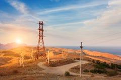 Torre ad alta tensione in montagne al tramonto Sistema del pilone di elettricità Fotografia Stock Libera da Diritti
