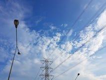 Torre ad alta tensione nel fondo nuvoloso del cielo blu con il lig della via Fotografie Stock Libere da Diritti