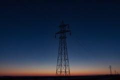 Torre alta de la transmisión contra puesta del sol azul hermosa foto de archivo libre de regalías