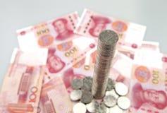 Torre alta delle monete con le banconote di yuan della porcellana Fotografia Stock