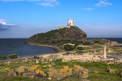 Torre antigua situada en una colina en el mar Mediterráneo con las ruinas de Tharros en el frente, Cerdeña, Italia fotografía de archivo libre de regalías