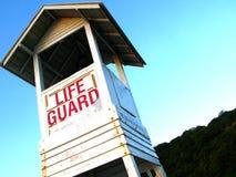 Torre bianca del bagnino sulla spiaggia contro cielo blu Fotografie Stock