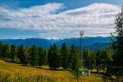 Torre cellulare di telecomunicazione nella foresta selvaggia con il fondo della montagna, l'Altai immagine stock libera da diritti