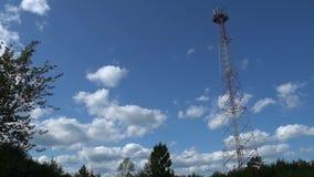 Torre celular de las comunicaciones con las nubes en día de verano Torre que transmite de la señal en lugar escénico Lapso de tie metrajes