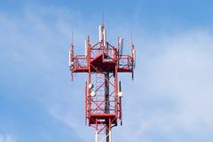 Torre celular roja y blanca con las antenas en azul Fotos de archivo