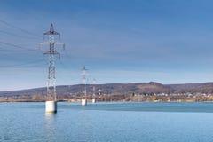 Torre d'acciaio della linea di trasmissione ad alta tensione sopra il fiume Fotografie Stock
