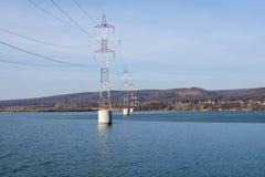 Torre d'acciaio della linea di trasmissione ad alta tensione sopra il fiume Fotografia Stock Libera da Diritti