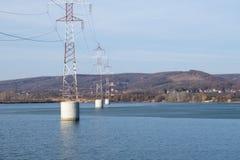 Torre d'acciaio della linea di trasmissione ad alta tensione sopra il fiume Fotografie Stock Libere da Diritti
