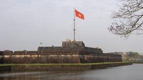 A torre da bandeira de Hue Citadel com a bandeira do voo de Vietname no vento imagem de stock