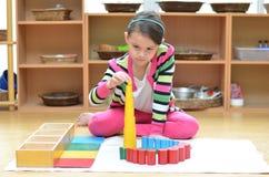 Torre da construção da mão da menina feita do montessori educacional Foto de Stock Royalty Free