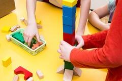 Torre da construção das crianças de blocos de madeira na tabela Fotografia de Stock Royalty Free