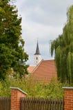 A torre da igreja vista longe no meio das árvores Foto de Stock Royalty Free