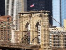Torre da ponte de Brooklyn com bandeira dos EUA, fundo das construções de Manhattan cedo na manhã com brilho do céu azul e do sol Imagens de Stock