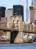 Torre da ponte de Brooklyn com bandeira dos EUA, fundo das construções de Manhattan cedo na manhã com brilho do céu azul e do sol Imagem de Stock