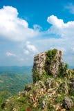 Torre da rocha ou da pedra com nuvem branca e o céu azul e para borrar o vale cênico da paisagem abaixo imagem de stock