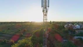 A torre da telecomunicação, a opinião do zangão na antena celular com o homem na veste da segurança e o capacete de segurança obt video estoque