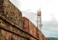 Torre da telecomunicação, parede velha e fundo nebuloso do céu em s Foto de Stock Royalty Free
