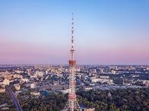 Torre da televisão no fundo da cidade, opinião do olho do ` s do pássaro, por do sol urbano na cidade Fotografia de Stock Royalty Free