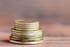 Torre das moedas em um fundo de madeira Pena, eyeglasses e gráficos Dinheiro closeup Imagens de Stock Royalty Free