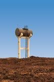 Torre de água em um fundo azul imagem de stock royalty free