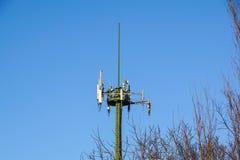 Torre de aço da telecomunicação com as antenas sobre o céu azul e as árvores Imagens de Stock Royalty Free