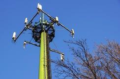 Torre de aço da telecomunicação com as antenas sobre o céu azul e as árvores Imagem de Stock