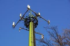 Torre de aço da telecomunicação com as antenas sobre o céu azul e as árvores Fotos de Stock Royalty Free