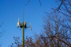Torre de aço da telecomunicação com as antenas sobre o céu azul e as árvores Imagem de Stock Royalty Free