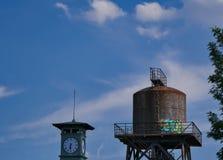 Torre de agua vieja con una torre de reloj en el primero plano imagen de archivo libre de regalías