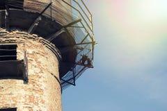 Torre de agua vieja y oxidada en un fondo del cielo claro azul foto de archivo