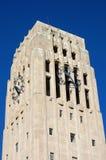 Torre de alarma del carillón con el reloj contra el cielo azul Fotos de archivo libres de regalías