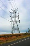 Torre de alta tensão da linha de alta tensão com a estrada no forground imagem de stock royalty free