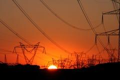 Torre de alto voltaje de la transmisión durante puesta del sol imagen de archivo