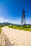 Torre de alto voltaje de las líneas eléctricas en montañas Imagen de archivo