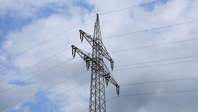 Torre de alto voltaje en fondo del cielo azul con las nubes de movimiento lento metrajes