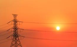 Torre de alto voltaje en tiempo de la puesta del sol Fotografía de archivo