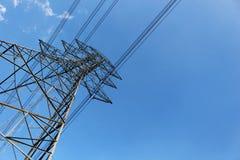 Torre de alto voltaje o línea de transmisión eléctrica con el cielo azul y la nube blanca imagenes de archivo