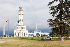 Torre de Chacha con la bandera nacional de Georgia cerca de ella Foto de archivo