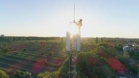 Torre de comunicación con el contratista que comprueba la conexión móvil encima de la antena celular en fondo del cielo azul con almacen de metraje de vídeo