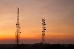 Torre de comunicación en fondo de la puesta del sol Imagenes de archivo