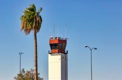 Torre de control del aeropuerto con el acompañamiento de los postes de la palmera y de la lámpara foto de archivo libre de regalías