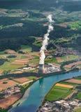 Torre de enfriamiento cerca del río El vapor sale de torre de enfriamiento Una visión aérea desde el avión imagenes de archivo
